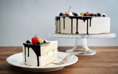 Fruit birthday cake  with cake slice over blue background